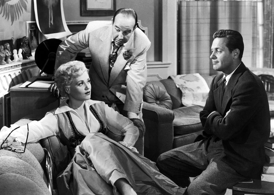 Judy Holliday and William Holden exchange knowing glances as Broderick Crawford leans in.