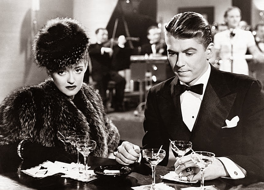 Judith (Bette Davis) shares a dreary drink with playboy companion Alec Hamm (Ronald Reagan).