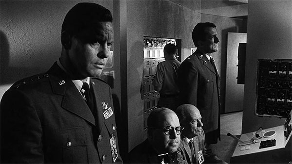 Concerned Strategic Air Command (SAC) commander General Bogan (Frank Overton), Mr. Foster (Dana Elcar), electronics expert Gordon Knapp (Russell Collins), and stolid Colonel Cascio (Fritz Weaver) watch disturbing developments from SAC Headquarters.