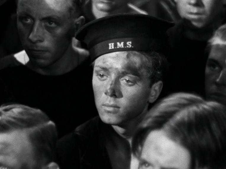 Young gunner (Richard Attenborough) listens contemplatively as the captain addresses the crew.