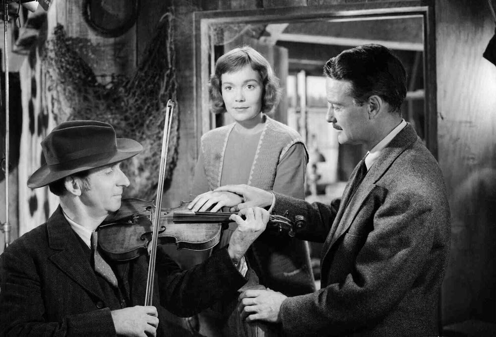 Dr. Robert Richardson (Lew Ayres) shows deaf-mute Belinda McDonald (Jane Wyman) how to hear the violin through her hand.