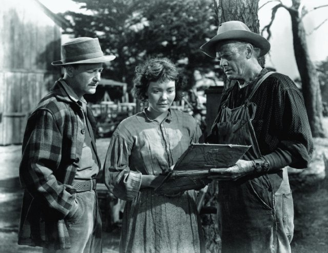 Dr. Richardson (Lew Ayres), Belinda (Jane Wyman), and her father Black MacDonald (Charles Bickford) view an album at the farm.