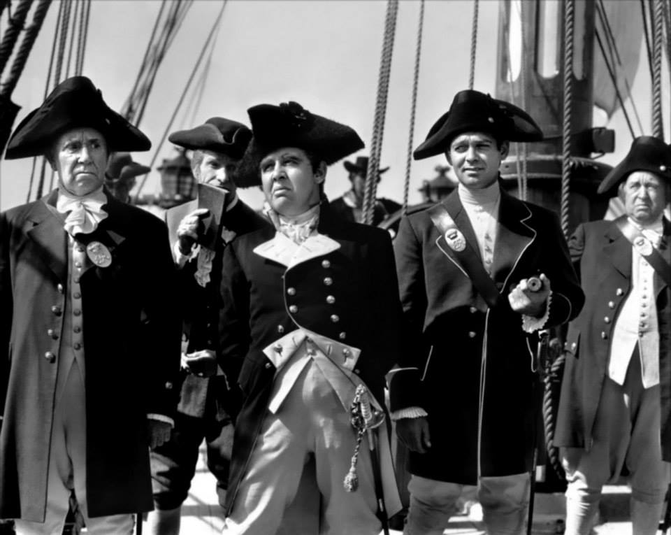 Captain Bligh (Charles Laughton) and ship's lieutenant Fletcher Christian (Clark Gable) surrounded by officers of the HMS Bounty