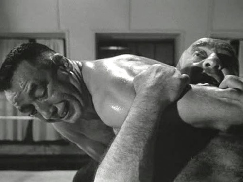 The Strangler (Mike Mazurki) has Gregorius the Great (Stanislaus Zbyszko) in a brutal choke hold, but who will prevail?