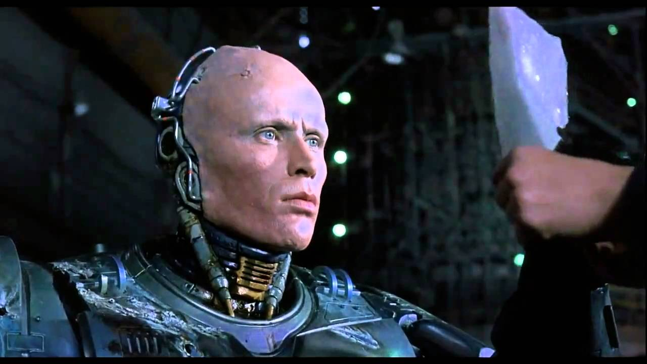Robocop (Peter Weller) sees his true face in a reflective shard.