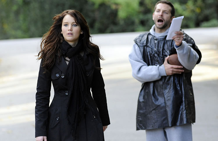 Tiffany Maxwell (Jennifer Lawrence) walks away from Pat Solitano, Jr. (Bradley Cooper) as he rants with a letter in one hand and a football in the other.