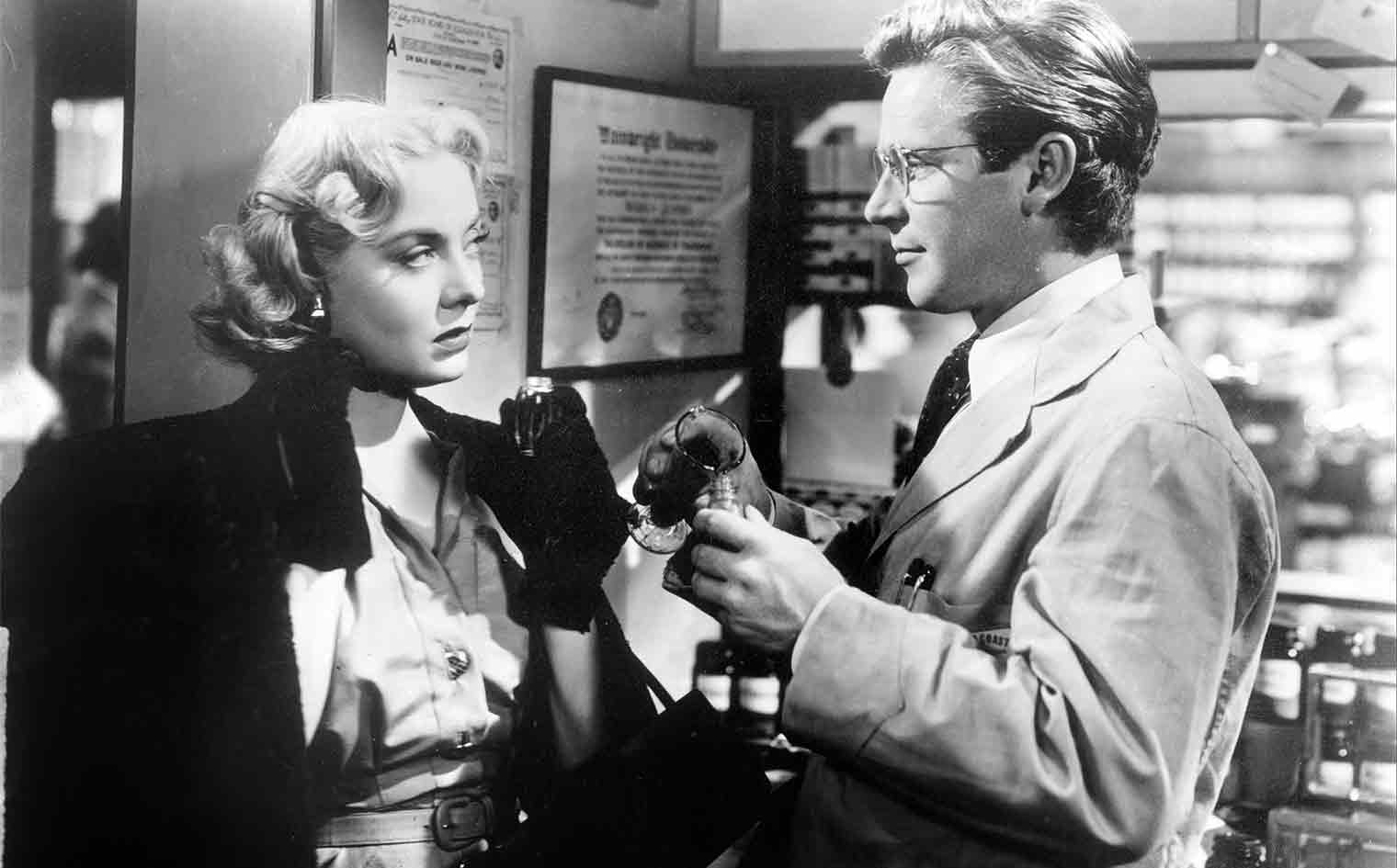 Cheatin' wife Claire Quimby (Audrey Totter) stares defiantly at Warren Quimby (Richard Basehart), her meek, bespectacled, pharmacist husband.