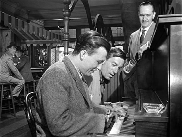 Homer Parrish (Harold Russell) accompanies Uncle Butch (Hoagy Carmichael) on the piano as Al Stephenson (Fredric March) looks on. In the background (deep focus), Fred Derry (Dana Andrews) is making a phone call.