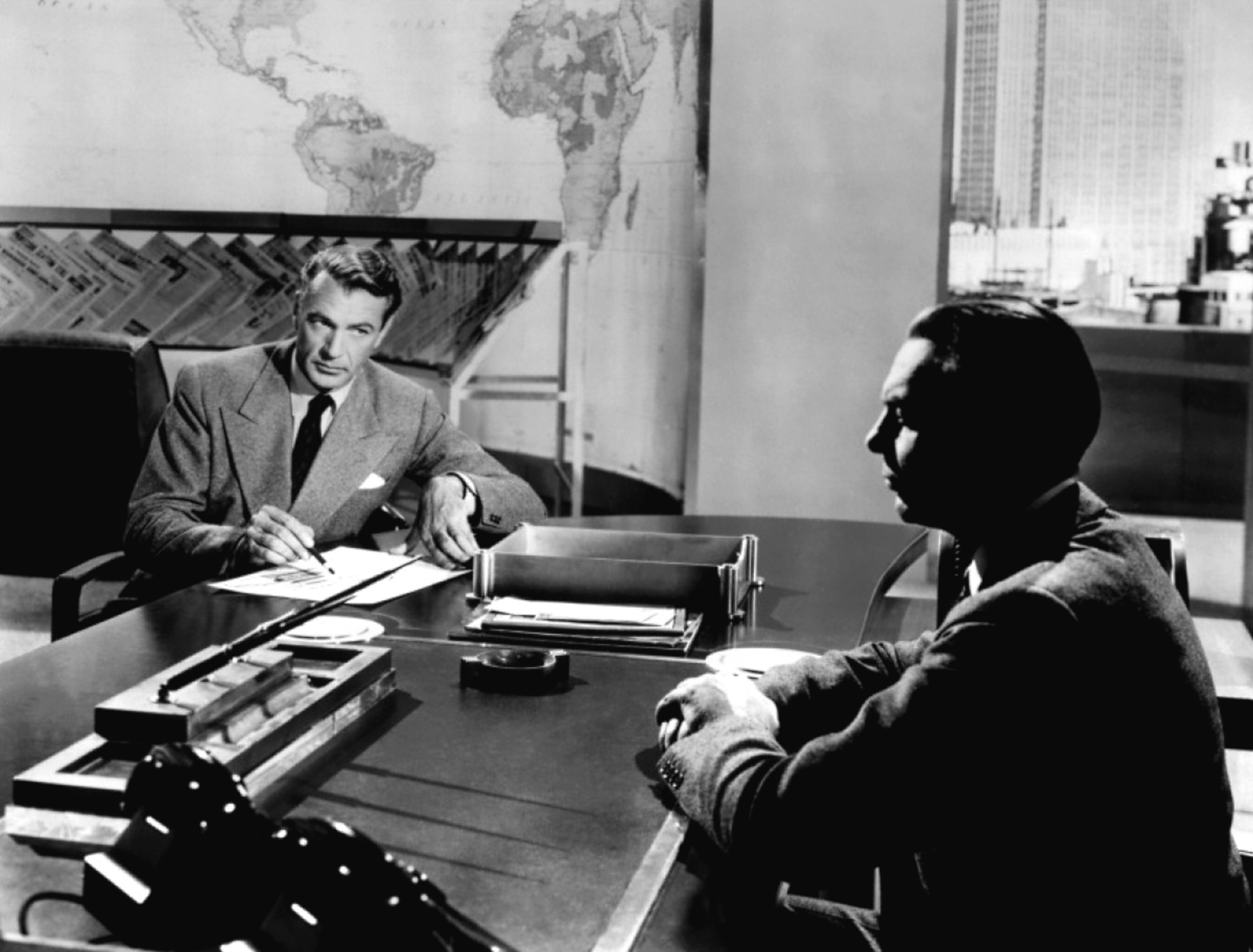 Howard Roark (Gary Cooper) discusses an ambitious building project with sullen publisher Gail Wynand (Raymond Massey).