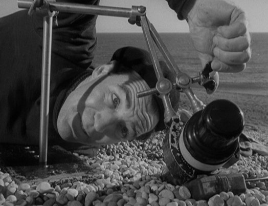 Sammy Rice (David Farrar) secures the booby-trapped device in preparation for attempting to disarm it.