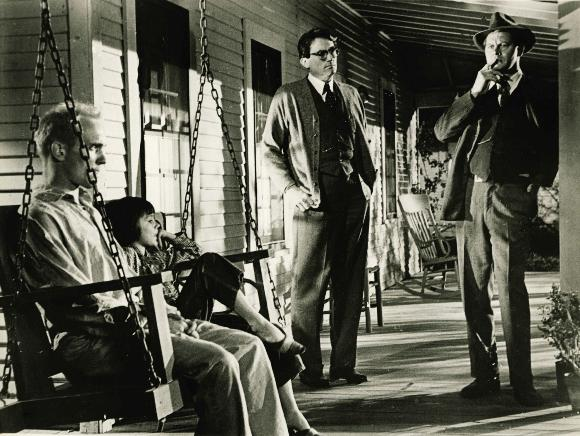 Boo Radley (Robert Duvall) sits quietly with Scout (Mary Badham) as Atticus Finch (Gregory Peck) and Sheriff Heck Tate (Frank Overton) ponder their course of action.