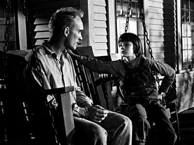 Boo (Robert Duvall) and Scout (Mary Badham) have a conversation on the bench swing.